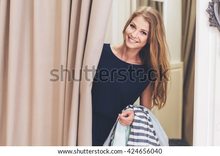 Can you bring me on more dress please! Beautiful young woman holding clothing and looking at camera with smile while standing in fitting room at the store - stock photo