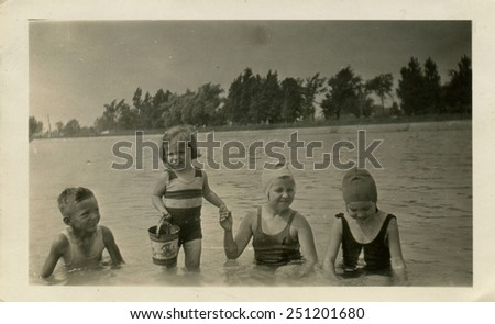 CANADA - CIRCA 1930s: Reproduction of an antique photo shows children, three girls and a boy sitting on a shelf or whether the river, or lake - stock photo