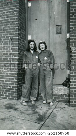 CANADA - CIRCA 1940s: Reproduction of an antique photo shows Two girls in denim overalls standing near the door of a brick industrial building - stock photo