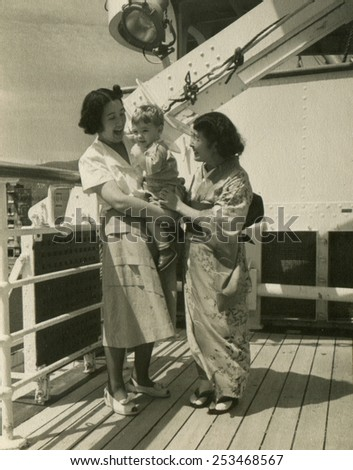CANADA - CIRCA 1950s: Reproduction of an antique photo shows Two Japanese women on the deck of the ship, one of them holding a Caucasian boy, the other wearing a kimono, both laughing