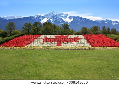 Canada flag done in red and white begonia flower against a backdrop of the Rocky mountains.  - stock photo