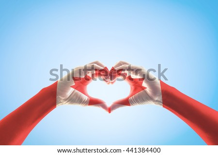 Canada flag pattern on people hands in heart shaped form isolated on blue sky background: National Canadian red maple leaf symbol for Canada labour day, veterans day, commonwealth holiday concept - stock photo
