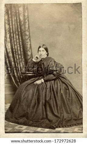 CANADA - HALIFAX - CIRCA 1861 - A vintage Cartes de visite photo of beautiful pioneer woman sitting in chair. She is dressed in hoop skirt dress.  Photo from the Civil War Victorian era. CIRCA 1861 - stock photo