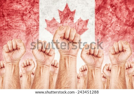 Canada Labor movement, workers union strike concept with male fists raised in the air fighting for their rights, Canadian national flag in out of focus background. - stock photo
