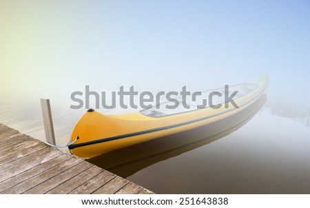 Canadian canoe moored in lake on foggy morning - stock photo