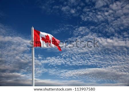 canadian flag against blue sky - stock photo