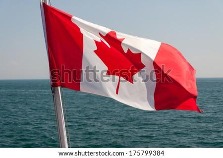 Canadian flag against Lake Ontario background - stock photo