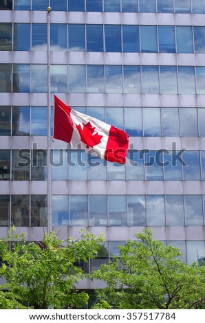 Canadian flag flies at half mast in front of government building - stock photo