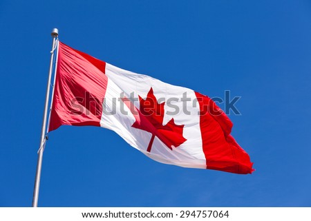 Canadian flag flying in light breeze on top of metal pole against blue sky - stock photo