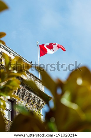 Canadian Flag Flying in Sky Over Government Building - stock photo