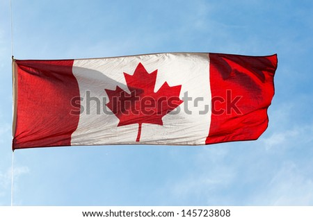 Canadian Flag in the wind against the sky