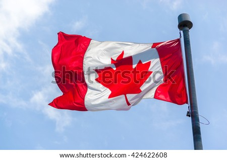 Canadian Flag in the wind over blue sky with clouds - stock photo