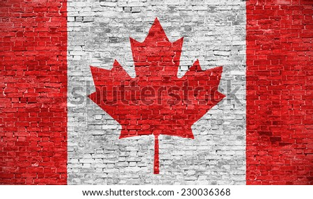 Canadian flag over old brick wall - stock photo