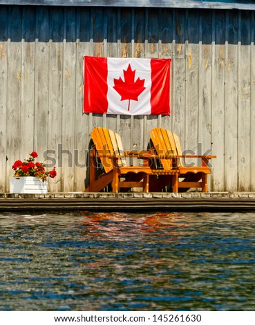 Canadian flag over two wooden chairs
