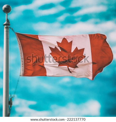 Canadian Flag Square. A Canadian flag attached to a flag pole with blue skies behind it. Edited in a vintage film like style. - stock photo