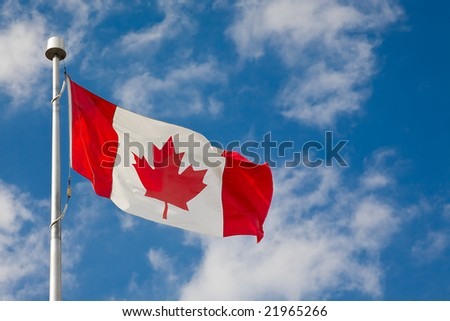 Canadian flag waiving against blue sky with few clouds - stock photo
