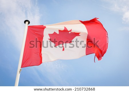Canadian flag waving against blue sky - stock photo
