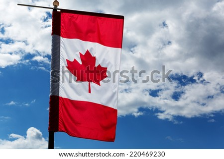 canadian maple leaf flag with cloudy sky in the background - stock photo