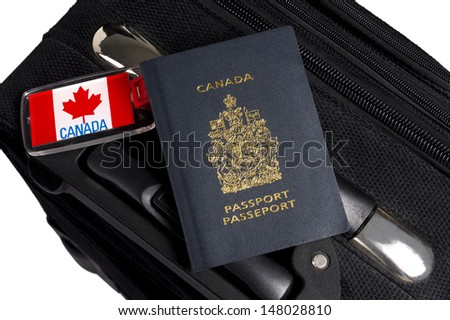 Canadian passport sitting on suitcase with maple leaf luggage tag - stock photo