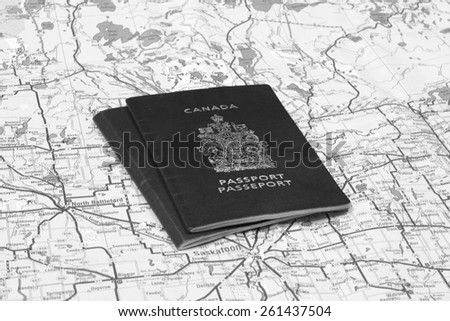 Canadian Passports on a map in black and white - stock photo