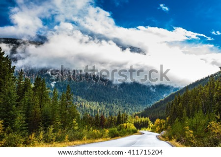 Canadian Rockies. Beautiful September day. Great Highway is among the mountains and forests yellowed - stock photo