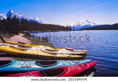 Canadian Rocky Mountains in the distance with kayaks at the lake edge - stock photo