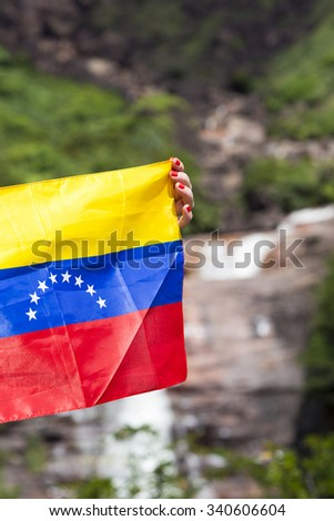 CANAIMA NATIONAL PARK, VENEZUELA, APRIL 11: The Venezuelan flag in the woman hands with the Angel Fall in the background, Venezuela 2015. - stock photo