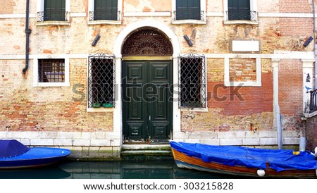 canal and boats with ancient brick wall house elements in Venice, Italy - stock photo