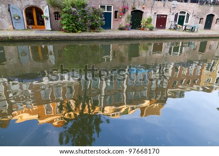 Canal and cellar wharfs in Utrecht, Netherlands. Vintage houses reflecting in water at sunset. - stock photo