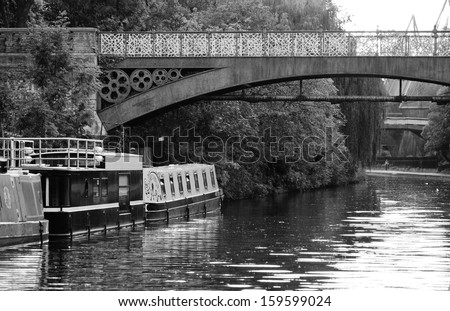 canal barge on canal river in Regents park London with bridge over