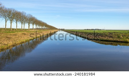 Canal in a rural landscape in winter - stock photo
