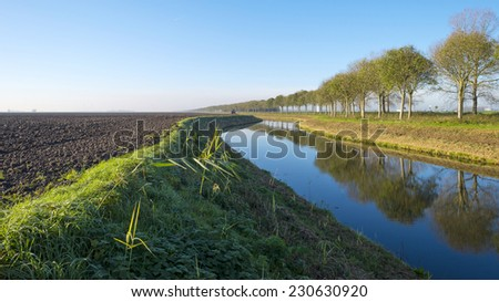 Canal in a rural landscape under a clear sky at fall - stock photo