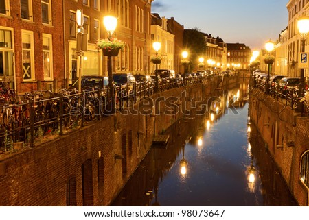 Canal in Utrecht, Netherlands. Houses, bicycles  and vintage street lamps along the canal at sunset.