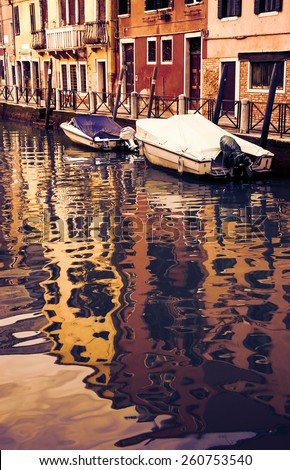 Canal in Venice. Boats and reflection of houses in the water. Toned photo. - stock photo