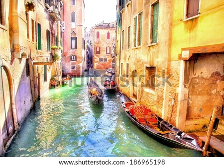 canal in venice with the colorful ancient buildings and houses at the waterside and gondola's on the canal in Italy  - stock photo