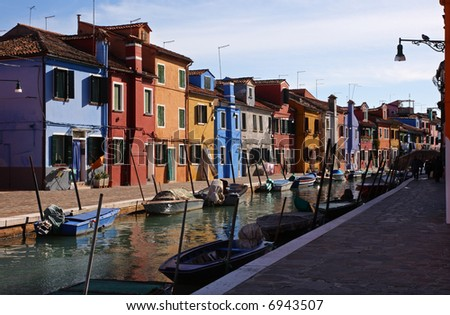 Canal on the island of Burano, near Venice, Italy. The water is flanked by small boats and multi-colored houses. - stock photo