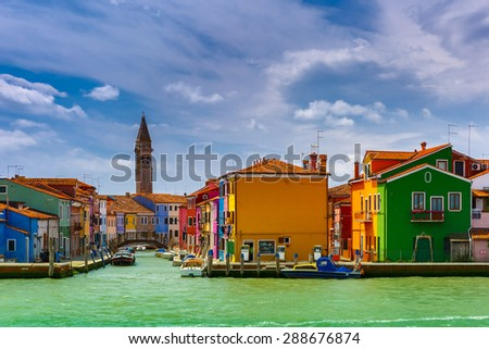 Canal with colorful houses, church, boats and bridge on the famous island Burano, view from the sea, Venice, Italy - stock photo