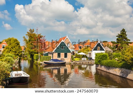 Canal with houses in the small Dutch village of Hindeloopen in Friesland - stock photo
