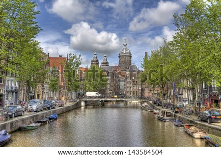 Canal with trees and a church in Amsterdam, Holland