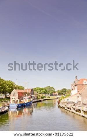 Canals in old dutch town Enkhuizen with landmark dromedaris in the background. - stock photo