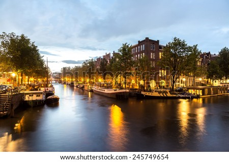 Canals of Amsterdam at night. Amsterdam is the capital and most populous city of the Netherlands - stock photo