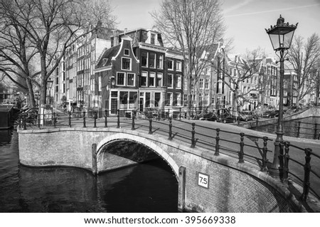Canals of Amsterdam, Netherlands. One of the typical bridges at the city center with houses at the background. Black and white