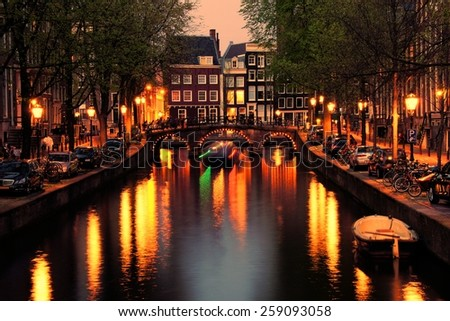 Canals of Amsterdam with bridge lit at night, Netherlands - stock photo