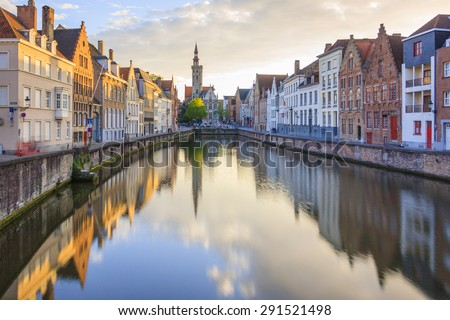 Canals of Bruges in a sunny spring afternoon with the church of our lady in the background, Bruges, Belgium - stock photo