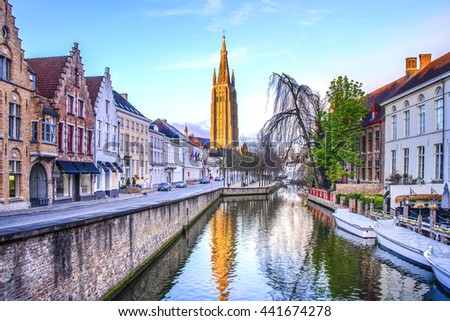 Canals of Bruges with the church of our lady in the background - stock photo