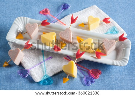"Canape on Valentine's Day romantic dinner ""Cupid's Arrow"" of sausage, cheese and a pepper on a white plate with napkin on a blue background, horizontal"