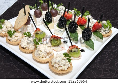 canape with cheese and berries on a plate in a restaurant