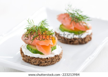 canape with cheese, cucumber and salmon, close-up - stock photo