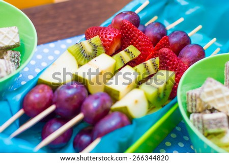Canape with fruits on the birthday party table - grapes, strawberries, pears, kiwi  - stock photo