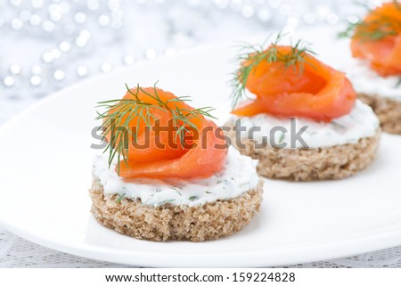 canape with rye bread, cream cheese, salmon and greens for the holiday, close-up - stock photo
